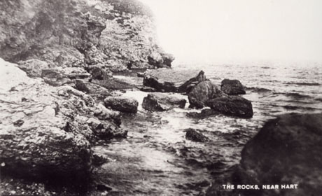 Postcard photograph entitled The Rocks, Near Hart showing the feet of cliffs and rocks in the sea at the feet of the cliffs; the rocks are currently known as Crimdon Rocks