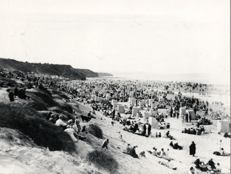 Photograph of Crimdon Beach crowded with people and showing cliffs in the distance, the beach and sand dunes in the foreground with tents or windbreaks