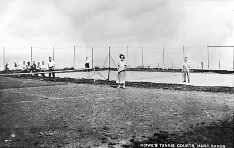 Postcard photograph entitled Howe's Tennis Courts, Hart Sands, showing two tennis courts side by side with the nets and wire fences round them; a woman in a dress is standing near the net in the court nearer the camera; nine figures can be seen standing at the edge of the court; two men in shirt sleeves and trousers are standing in the further court