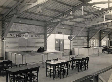 Photograph of a counter with the words Sundaes and Ices behind it and a counter with the word Confectionery behind it; in front of the counters are wooden tables and chairs; the girders and doors of the building can also be seen; the building has ben identified as The Pavilion, Crimdon Park, on its opening; the photograph was taken by T. G. Reeves, 351 London Road, Mitcham, Surrey