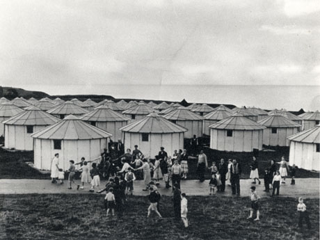 Photograph showing the roofs and exteriors of thirty nine round huts with conical roofs; only one small window can be seen in each hut; in front of the huts, groups of people and children are standing; the sea appears to be visible on the horizon; the huts have been identified as Council Alltents at Crimdon (Aluminium Tents)