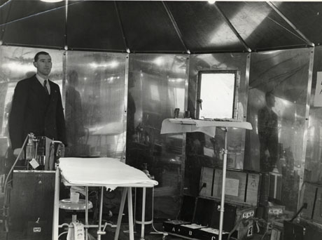 Photograph showing the interior of a structure made of metal, six panels of which and a window can be seen; inside the structure is a man in a suit standing next to what appears to be a machine for administering anaesthetics and next to what appears to be a treatment couch; under the couch a glass can be seen on a stool; on the right of the couch a stand with medical instruments can be seen; behind the stand is an open trunk with the letters F. S. P. on it; it contains three drawers labelled A B and C; it is possible that the photograph is depicting a dentist's surgery at Crimdon Dene