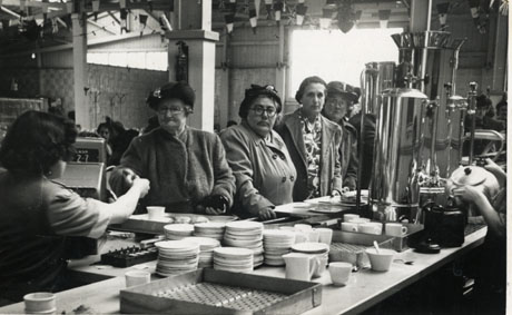 Photograph showing the surface of a self-service counter on which there are piles of plates, a water boiler and the hands of a server pouring water into a teapot; the rear of a woman working at a till giving change to a customer can also be seen; four middle aged women wearing hats and coats can be seen standing at the counter facing the camera