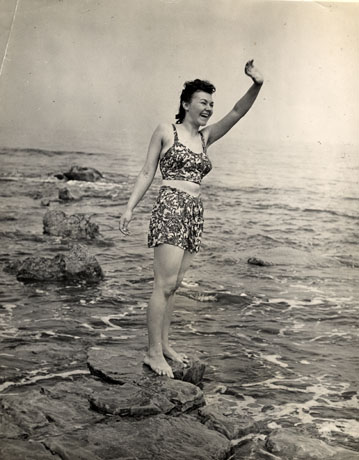 Photograph showing a young woman in a bathing costume standing on a rock in the shallows of the sea waving to a person out of sight to the right of the camera; the photograph has been identified as having been taken at Crimdon Dene