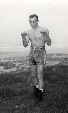 Photograph of a man wearing boxing trunks with M. C. on them, standing, with his fists raised, on grass with the sea in the background; he is wearing a trophy belt; he has been identified as Maurice Cullen, Lightweight Champion of Great Britain