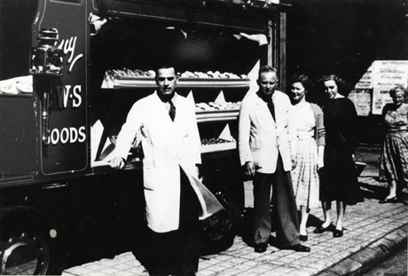Photograph of a delivery van with the legend Buy C.W.S. Goods on its side; the van's side is open showing trays of cakes; a man in an overall is standing in front of the van and another man and three women are standing near the van, possibly wishing to purchase items; the photograph has been described as Haswell Branch of Sherburn Hill Co-op, circa 1951