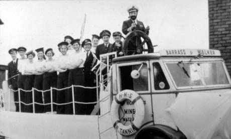 Photograph showing fourteen women in naval uniform standing on a lorry, behind decoration made to resemble the side of a ship; a woman behind the cab of the lorry is wearing a beard, and male naval uniform, and is standing at the wheel of a ship; the lorry has the words, Barrass and Walker, above the cab; on the door of the cab the words Highways, Mines, Water can be seen, behind a lifebelt, which bears the words, H.M.S. R Tannin; they have been identified as members of Haswell Women's Institute on a float with the title, Ship Ahoy