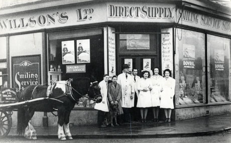 Photograph of the exterior of a shop on the corner of a road; above the windows are the words: Walter Willson's Ltd. Direct Supply. Smiling Service Shop; the doorway bears the words: Your Search For A Good Grocer Ends. Walter Willson's For Goods That Are Good...;in the road in front of the shop is a horse in the shafts of a cart bearing the words: Walter Willson's Ltd. Smiling Service; in the doorway, three women and two men in white overalls, a young girl and a young boy in overalls, are standing; they have been described as the staff of the shop