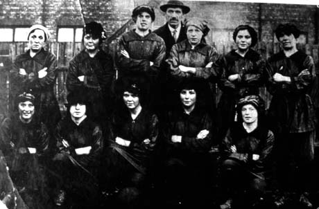 Photograph of eleven women in indistinct dark blouses and skirts, posed in two rows with a man wearing a overcoat, hat and tie; there are indistinct buildings behind them; they have been described as Ladies' Football Team, Horden
