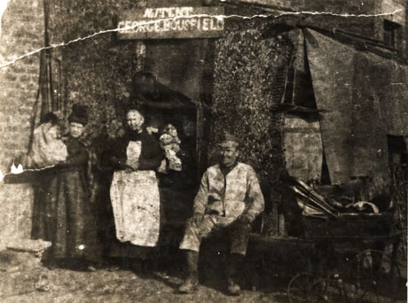 Photograph showing a tent erected against the side of a brick building; two women are standing in the opening of the tent; one of the women appears to be carrying a small child; a man wearing a hat and overalls is sitting to the right of the tent opening; on his right are a barrel and a perambulator; above the entrance is a sign reading: No.1 Tent George Bousfield