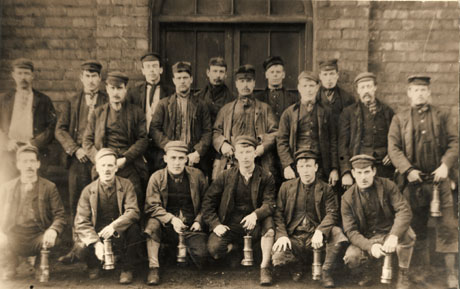 Photograph of twelve men standing against a brick wall and doorway; in front of them are six men squatting on the floor; they are wearing jackets, caps, breeches, scarves, waistcoats, and are carrying miner's lamps and have been identified as a group of miners