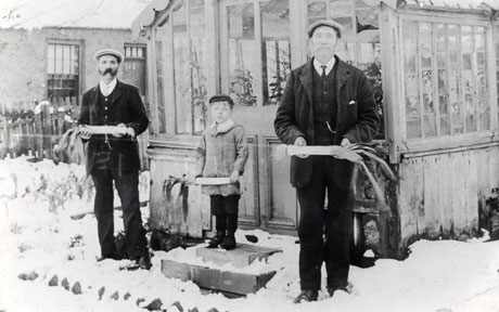 Photograph of two men standing either side of the step at the entrance to a greenhouse, on which a small boy, aged approximately seven years, is standing; the men are wearing suits, ties and caps, and the boy is wearing a cap, dark trousers and a light coat; they are all holding large competition leeks; the greenhouse, facades of houses and the ground, under snow, can be seen; they have been identified as being at Esh Winning