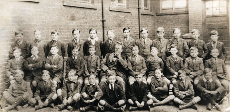 Photograph showing thirty one boys, aged approximately eleven years, posed in three rows against the walls of a brick building; a man in a suit and academic gown is sitting in the middle of the middle row; they have been identified as pupils at Henry Smith School, Hartlepool