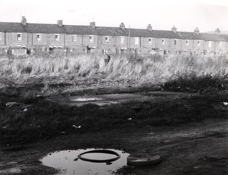 Photograph showing, in the foreground, an expanse of earth with rough grass beyond it; beyond that is the rear of a terrace of houses