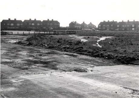 Photograph showing cracked concrete and rough waterlogged earth with sixteen semi-detached houses beyond in the distance