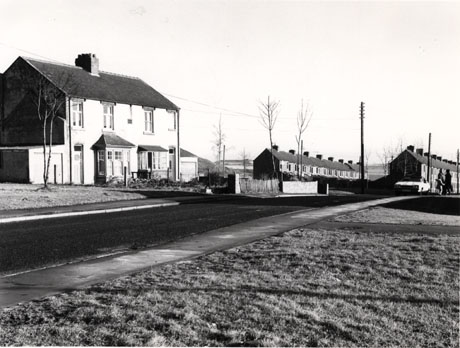 Photograph showing, on the left of the picture, semi-detached houses with bay windows and attached garages; on the right of the picture are two terraces running away from the camera to the right; beyond the houses, open countryside can be seen