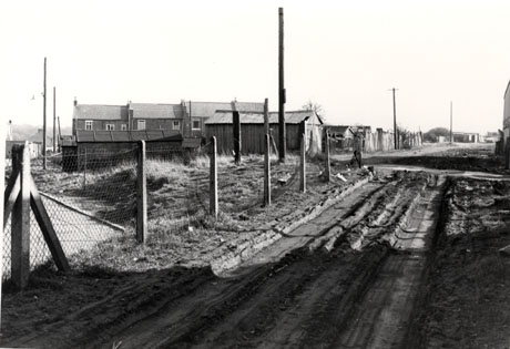 Photograph showing a rutted track through mud, leading away from the camera to the right into a field; on the left is a wire fence with sheds beyond it; behind the sheds are the backs of three terraced houses with other houses in the distance