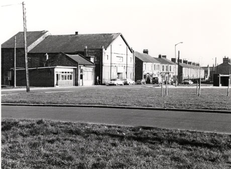 Photograph of the exterior of two small shops next to a large building, used as a club, with three cars parked outside; beyond the garage are five small shops; beyond the shops is a terrace of houses; a van and two cars are parked outside the shops and houses; there are two pieces of grass on either side of a road in the foreground; the buildings are the same as those in misc0069