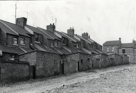 Photograph of the rear of five terraced houses, showing the back yard walls, outhouses, kitchen roofs, and first floor windows; a cobbled road and open space where houses may have been demolished