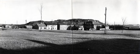 Photograph showing an expanse of mown grass with saplings on it; at the far side of the green are huts, six houses and a large building, possibly a public house; behind the buildings are fields and, possibly, a pit heap