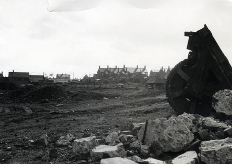 Photograph showing a pile of stones at the right of the front of the picture with a metal wheel with a serrated edge; beyond the pile of stones is an area of cleared ground with the traces of caterpillar tracks in it; beyond that, on the right, are the roofs of terraced houses and, in the centre the top of a double-decker bus; other buildings can be seen on the left