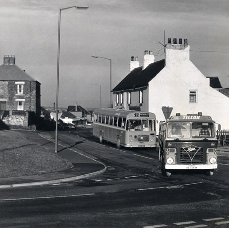 Photograph showing a lorry with the words Foden and Tilcon on it and the registration, RAJ 264M, driving round a bend in a road towards the camera; a bus with the word Peterlee, and the number 215, on its direction board, is following the lorry round the bend; a large white building, possibly a public house, is on the right of the road; grass and, beyond it, a house can be seen; buildings and distant countryside can be seen in the centre of the picture