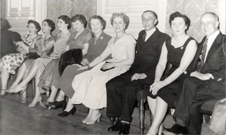 Photograph of seven women and two men seated on chairs against a wall in a room with mouldings and luxurious wallpaper on the wall behind them; the women are wearing formal dresses and the men lounge suits; they have been identified as Dawdon Officials at a Dance