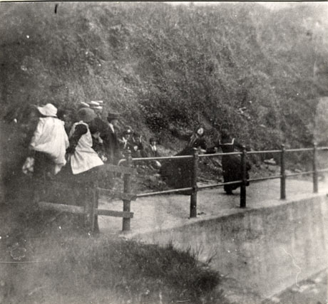 Photograph of a slope covered in vegetation on the left of the picture; in the centre is a concrete path with an iron railing along its length; two girls in pinafores are sitting on the left of the railing with their backs to the camera; two girls wearing long dark dresses are running along the path behind the railings; approximately eight people are watching the girls from the slope; the place has been identified as Dalton le Dale