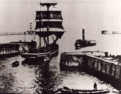 Photograph of a small ship with three sails departing through the entrance to Seaham Harbour; the moles of the harbour can be seen on either side of the ship; a steam tug is approaching the harbour from the open sea; a small boat can be seen at the bottom right of the picture; the photograph has been described as A Collier Brig in Seaham Docks