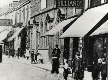 Photograph, close-up, of the facade of a building with large and imposing windows and with a sign advertising billiards; on either side of that building are shops with awnings; a sign reading, possibly, [ ]minsk, can be seen on the wall beyond the large building and its adjacent shop;the shops have been identified as being on Church Street, Seaham