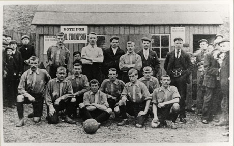 Photograph of eight men kneeling on the ground wearing shorts and shirts, with stars on them; behind the eight men are two others with the same costume and man in a jumper; approximately twenty young men and boys are watching the proceedings; the men are in front of a hut on which there are posters advertising an election and exhorting the populace to Vote For Thompson; the men have been identified as members of the White Star Football Team of Seaham