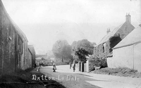 Photograph showing, on the left, the front of a line of buildings; in the centre of the picture there is a road in which there are a child and woman standing in front of a cottage on the right, which is covered with ivy; an indistinct building can be seen at the end of the road and a barn near the cottage, which has been described as Ivy Cottage, Dalton-Le-Dale