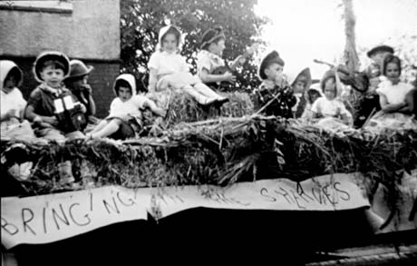 Photograph showing eleven children, wearing hats and dresses, aged approximately six years, sitting on straw, there is a banner reading Bringing In The Sheaves, beneath them; they have been described as being on a carnival float in Seaham
