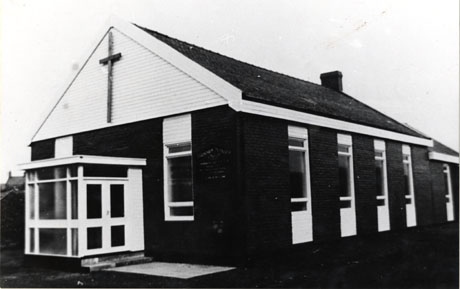 Photograph of the exterior of a single-storey building with six windows down its side and a porch and two windows on its front; above the porch is a large crucifix; the building is in a plain post Second World War style; it has been identified as the Independent Methodist Church at South Hetton